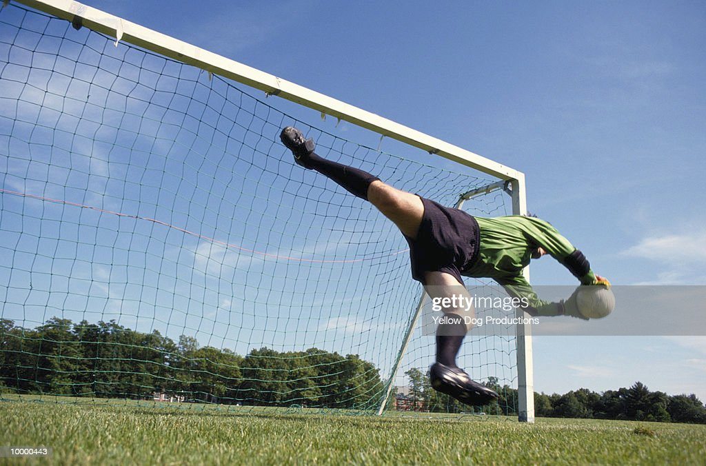 GOALIE DIVING FOR SOCCER BALL : Stock Photo
