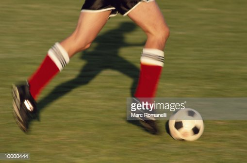 SOCCER PLAYER'S LEGS DRIBBLING BALL : Stock Photo