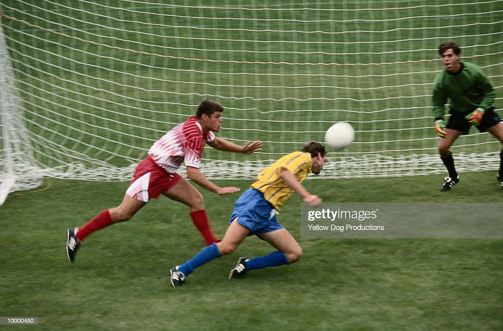 SOCCER PLAYER HITTING BALL WITH HEAD INTO NET : Stock Photo