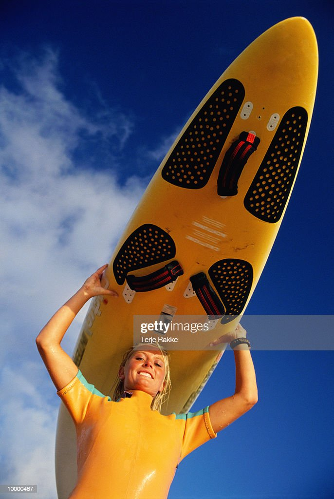 WOMAN CARRYING SURFBOARD OVER HEAD : Stock Photo