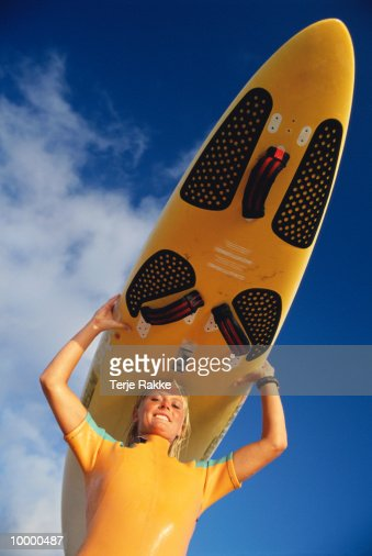 WOMAN CARRYING SURFBOARD OVER HEAD : Photo
