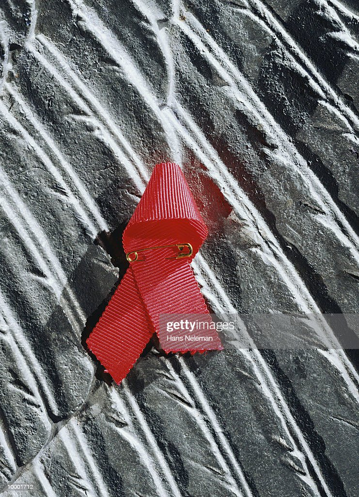 RED AIDS RIBBON ON GRAY RIPPLED BACKGROUND : Stock Photo