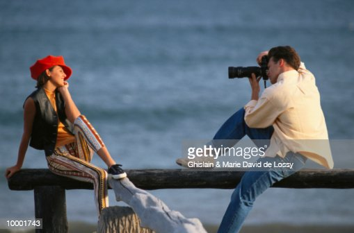 MAN PHOTOGRAPHING WOMAN NEAR WATER : Foto de stock