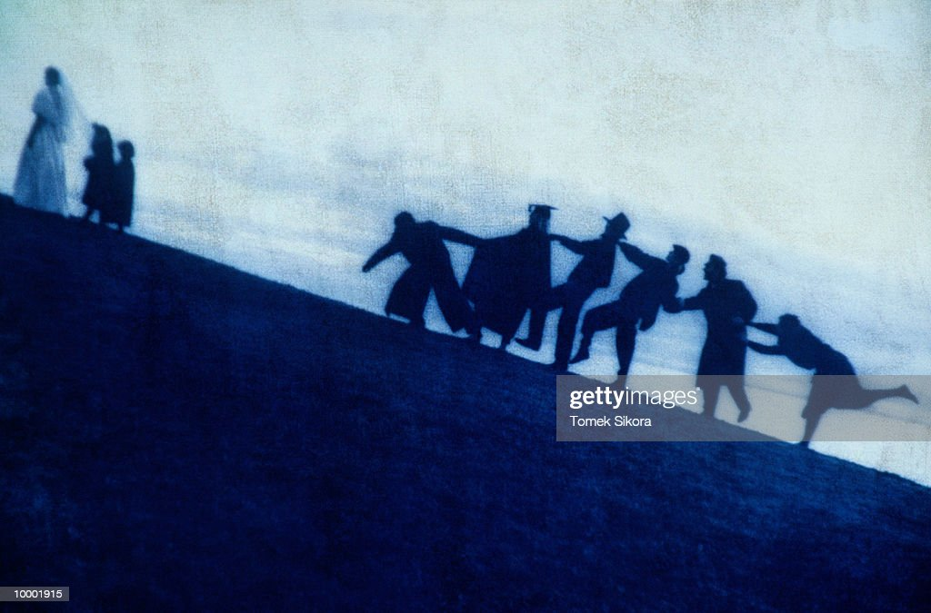 SILHOUETTE OF A BRIDE & PEOPLE WALKING UPHILL : Stock Photo