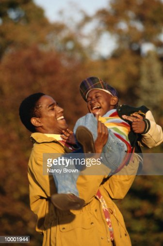 BLACK FATHER PLAYING WITH YOUNG SON OUTDOORS : Stock-Foto