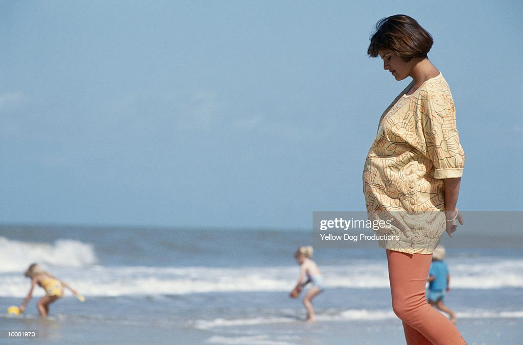 PREGNANT WOMAN WALKING ON BEACH : ストックフォト