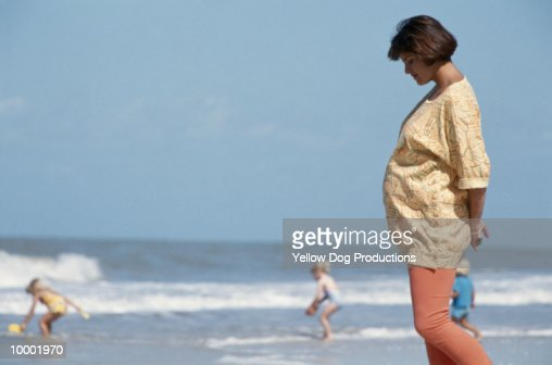 PREGNANT WOMAN WALKING ON BEACH : Stock-Foto