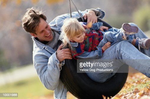 FATHER & DAUGHTER PLAYING ON TIRE SWING : Stockfoto
