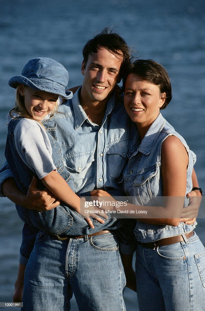 COUPLE HOLDING GIRL BY WATER : Stock Photo