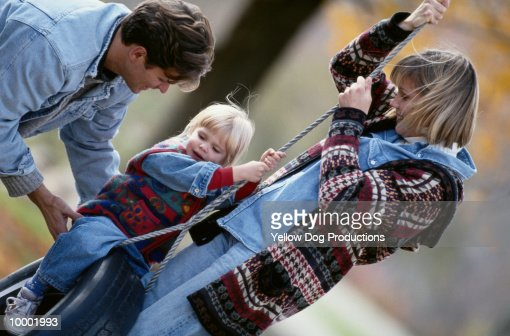 YOUNG FAMILY PLAYING ON TIRE SWING : Stock Photo