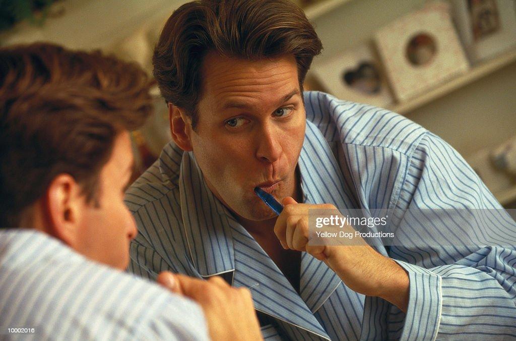 MAN BRUSHING TEETH IN MIRROR : Stock Photo