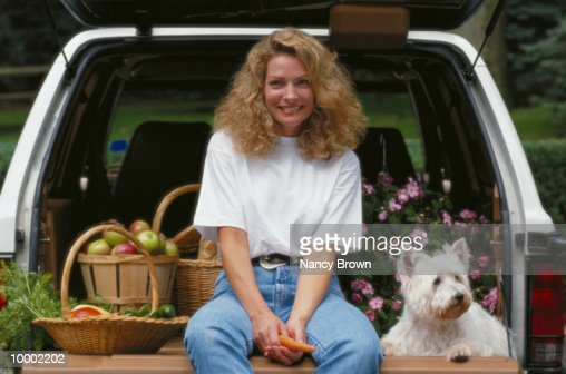 WOMAN SITTING ON TAILGATE WITH DOG : Foto de stock