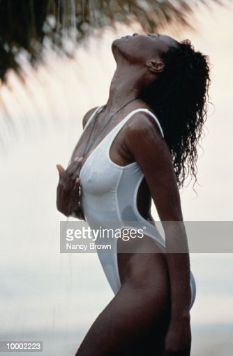 BLACK WOMAN SHOWERING IN SWIMSUIT ON BEACH : Stock Photo