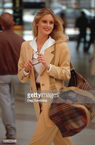 BLONDE WOMAN WALKING OUTDOORS WITH BAG : Stock Photo