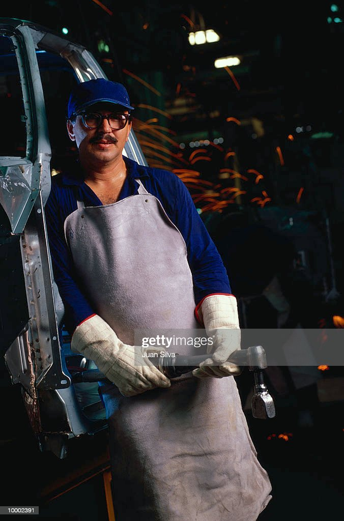 AUTO ASSEMBLY LINE WORKER WITH WRENCH : Bildbanksbilder