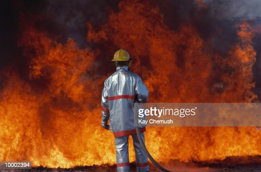 BACK VIEW OF A FIREFIGHTER WITH HOSE & FIRE : Stock-Foto