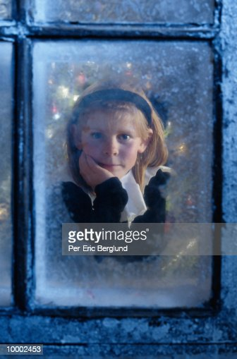 GIRL WATCHING FOR SANTA FROM ICY WINDOW : Photo