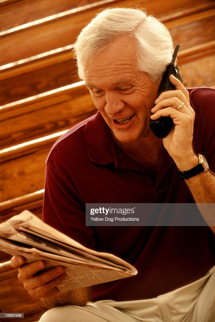 MATURE MAN ON PHONE WITH NEWSPAPER : Stock Photo