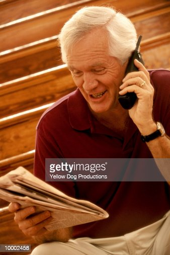 MATURE MAN ON PHONE WITH NEWSPAPER : Foto de stock
