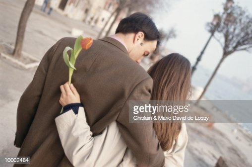 MAN & WOMAN WITH TULIP WALKING NEAR WATER : Photo