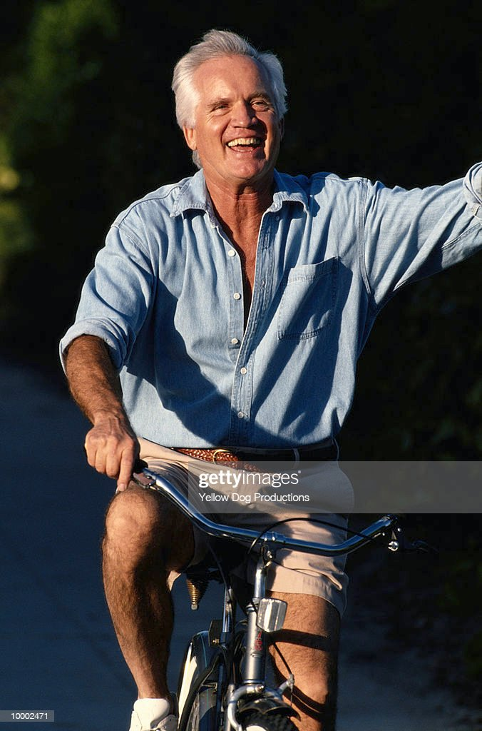 MATURE MAN WAVING ON BICYCLE : Stock Photo