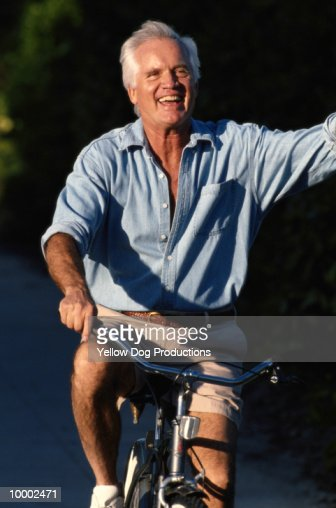 MATURE MAN WAVING ON BICYCLE : Stockfoto