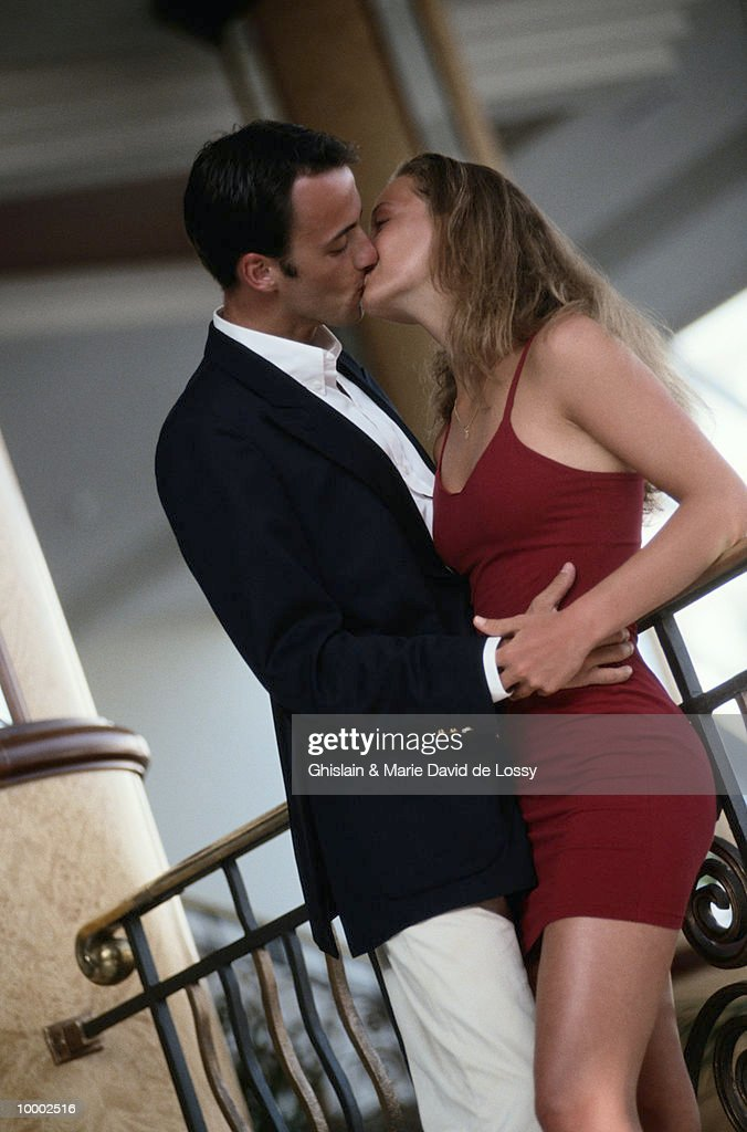 YOUNG COUPLE KISSING BY RAILING : Stock Photo