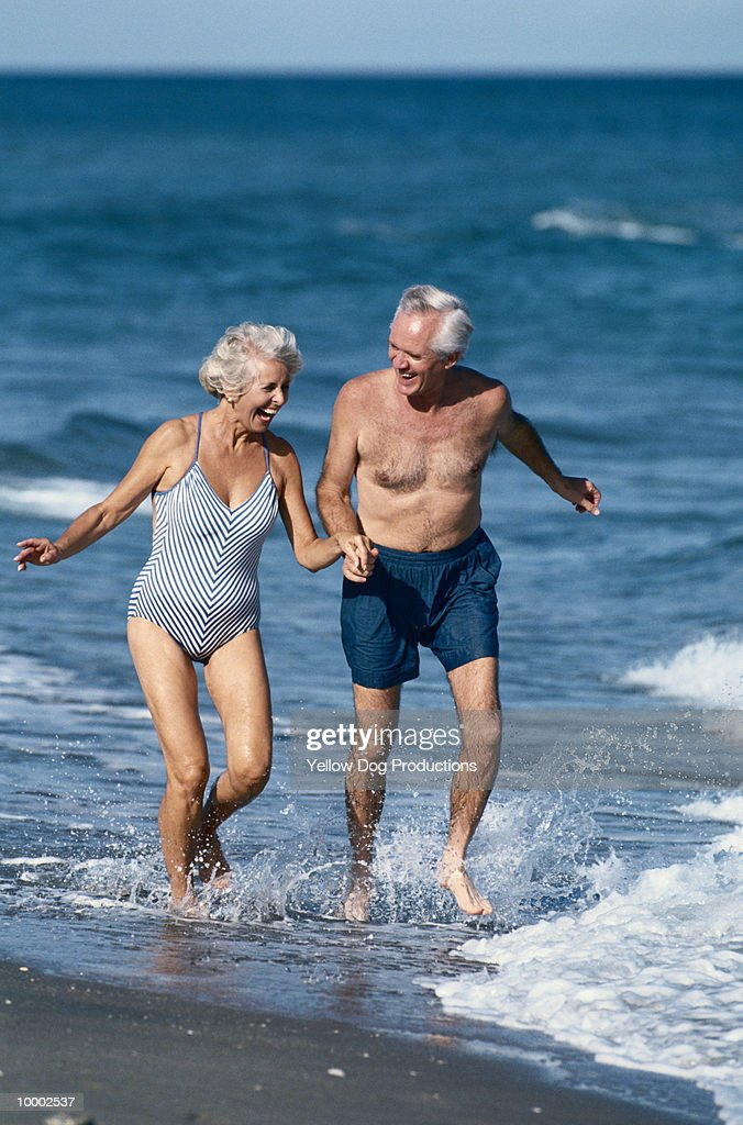MATURE COUPLE IN SWIMSUITS IN SURF : Stock Photo