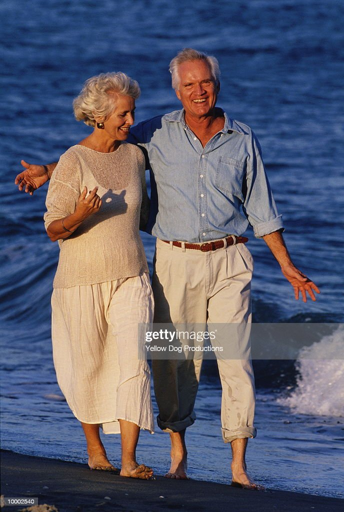 MATURE COUPLE WALKING IN SURF : Stock Photo
