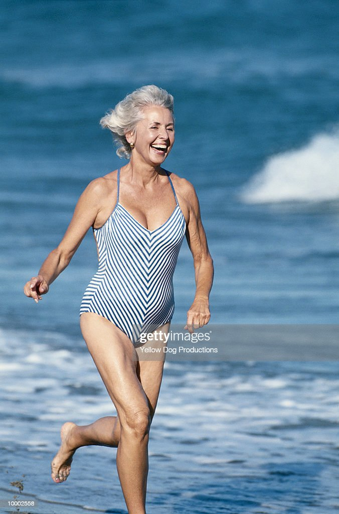 MATURE WOMAN RUNNING ON BEACH IN SWIMSUIT : Bildbanksbilder
