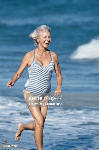 MATURE WOMAN RUNNING ON BEACH IN SWIMSUIT : Foto de stock