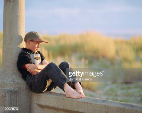 PENSIVE, BAREFOOT BOY SITTING IN OVERALLS : Stock-Foto