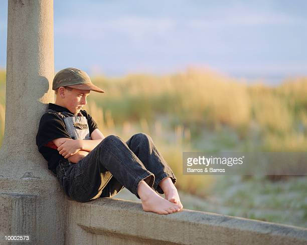 PENSIVE, BAREFOOT BOY SITTING IN OVERALLS