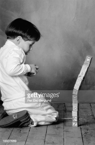 YOUNG BOY WITH STACKED BLOCKS IN BLACK AND WHITE : ストックフォト