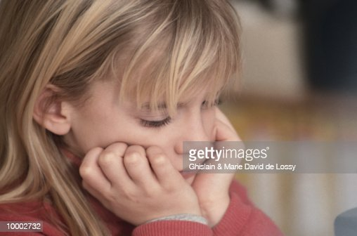 DISTRAUGHT GIRL WITH CHIN IN HANDS : Stock Photo