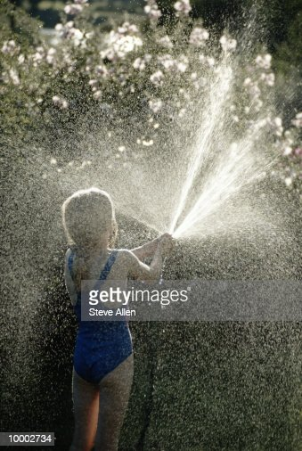 GIRL SPRAYING WATER HOSE : Photo