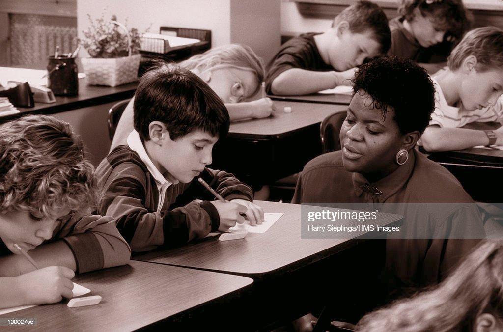 BLACK TEACHER WITH STUDENTS IN CLASS IN BLACK AND WHITE : Stockfoto