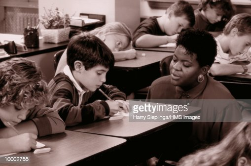 BLACK TEACHER WITH STUDENTS IN CLASS IN BLACK AND WHITE : Stock Photo