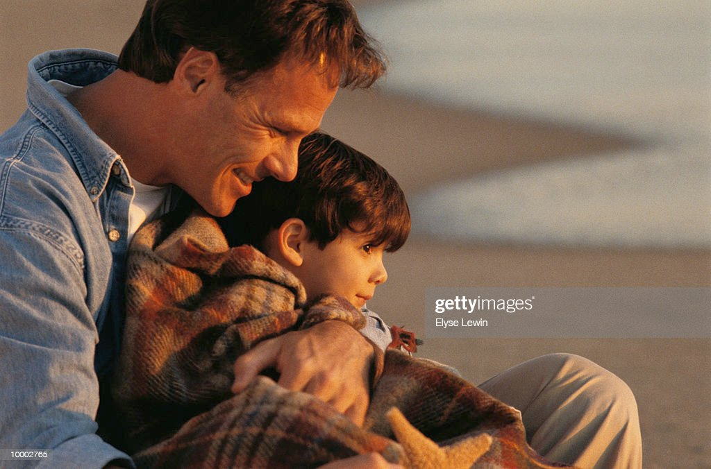 DAD WITH SON IN BLANKET AT BEACH : Stock Photo