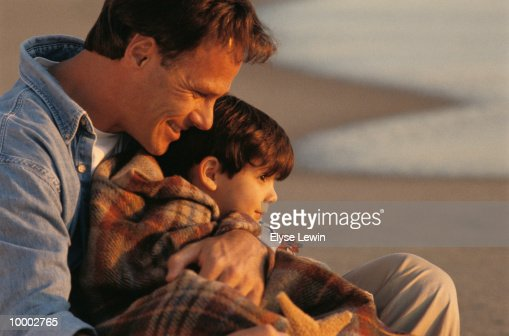 DAD WITH SON IN BLANKET AT BEACH : Foto de stock