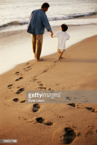 DAD & BOY WALKING ON BEACH WITH FOOTPRINTS : Bildbanksbilder