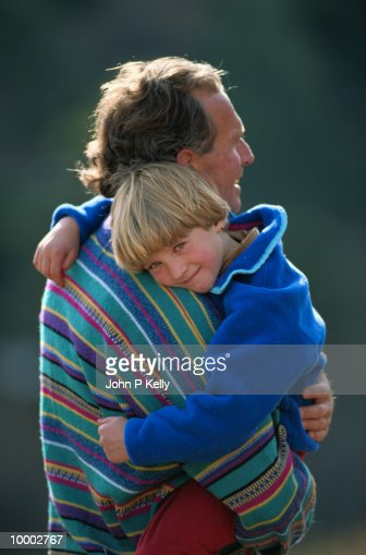 DAD HOLDING SON OUTDOORS : Stock Photo