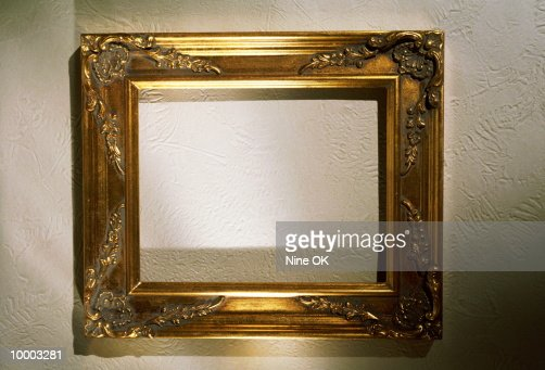 EMPTY GOLD PICTURE FRAME ON A WALL : Stock Photo