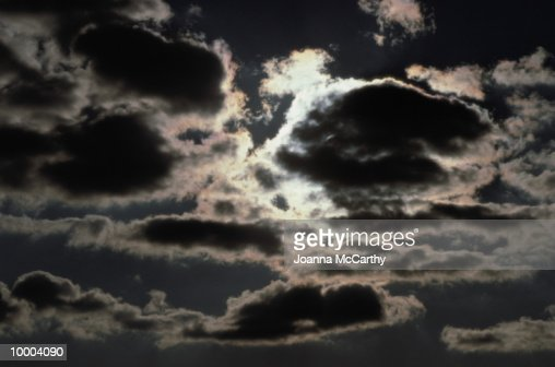 SUN SHINING BEHIND CLOUDS : Stock Photo