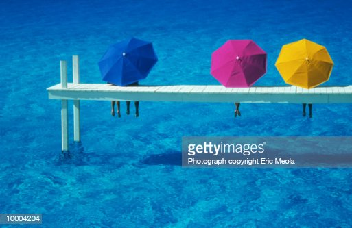 PEOPLE ON WHITE DOCK WITH COLORFUL UMBRELLAS : Stock Photo