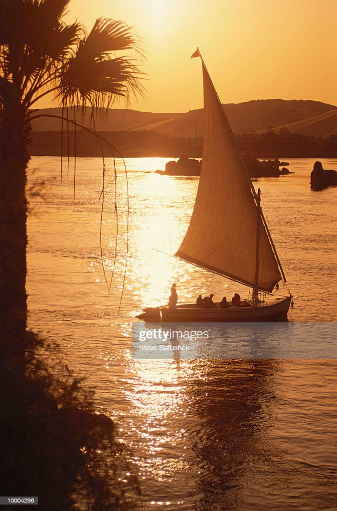 FELUCCAS AT SUNSET ON THE NILE RIVER IN ASWAN, EGYPT : Stock Photo