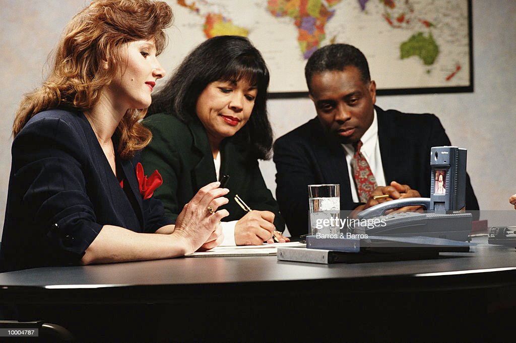 MULTI-ETHNIC BUSINESS MEETING WITH TV PHONE : Stock-Foto