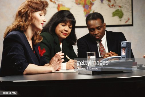 MULTI-ETHNIC BUSINESS MEETING WITH TV PHONE : Stock Photo