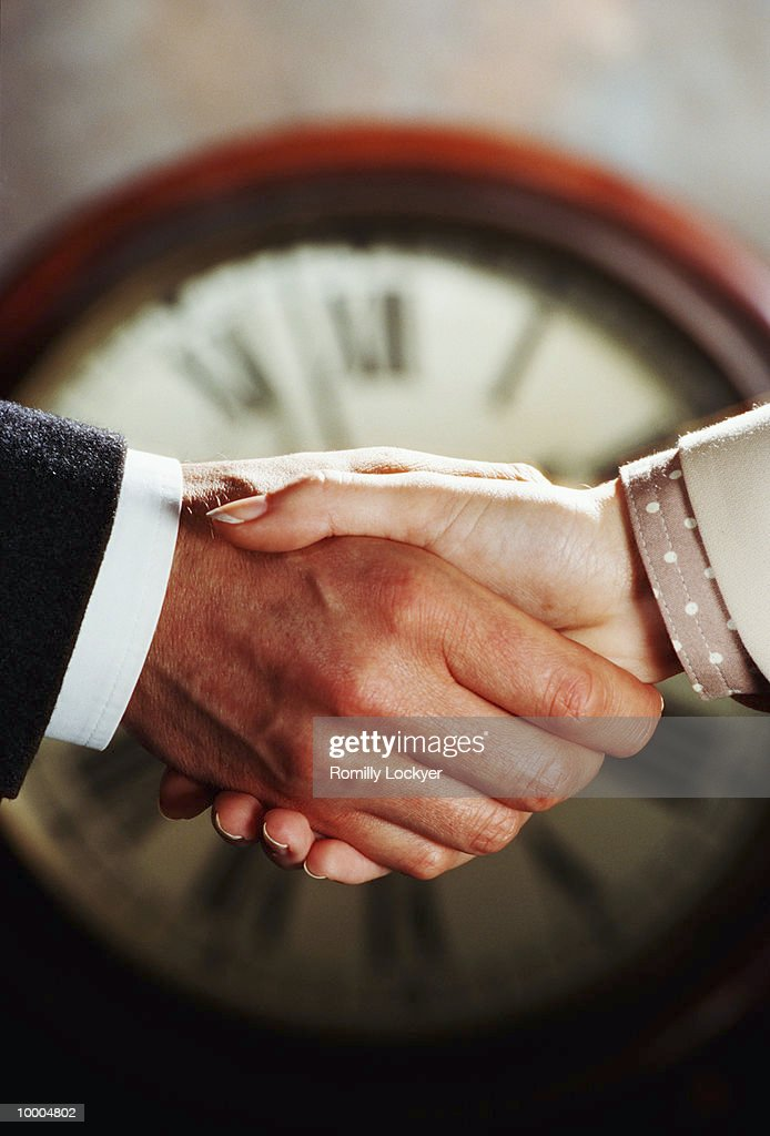 CLOCK BEHIND BUSINESS COUPLE'S HANDSHAKE : Stock-Foto