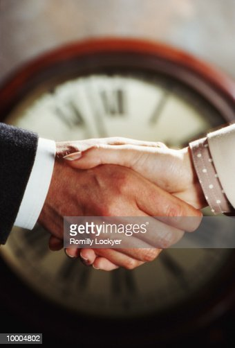 CLOCK BEHIND BUSINESS COUPLE'S HANDSHAKE : Bildbanksbilder